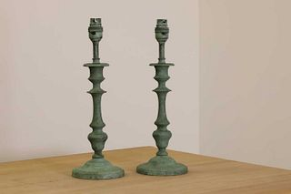 A pair of verdigris candlestick lamps,