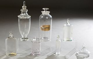 """Group of Six Glass Apothecary Items, early 20th c., consisting of a large circular stoppered drug jar, with a partial glass label for """"Flo. Arnica,"""" t"""