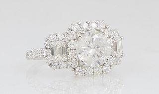 Lady's 18K White Gold Dinner Ring, with a central 2.03 carat round diamond, atop an octagonal border of round diamonds, flanked by diamond bordered lu