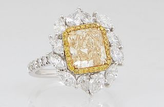 Lady's 18K White Gold Dinner Ring, with a 2 carat fancy yellow rectangular cut diamond, within a border of thirty tiny round yellow diamonds, atop a b