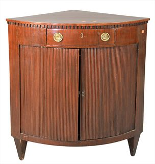 """Continental Mahogany Corner Cabinet, having one drawer over two faux tambour doors, opening to interior shelving, height 36 1/2 inches, top 25"""" x 35""""."""