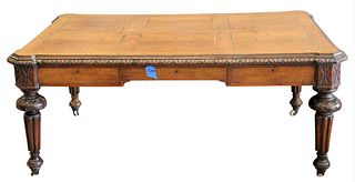 """Oak Library Table/Desk, having carved frame set on fluted legs and casters, height 29 inches, top 45"""" x 68""""."""