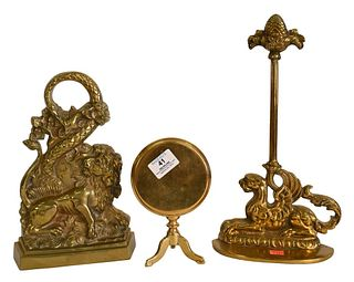 Three Piece Brass Group, to include Queen Anne brass trivet with tilt top, lion with serpent door stop, and a winged griffin doorstop, height 14 inche