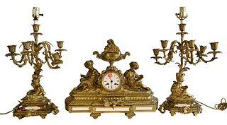 Three Piece Brass Mantle Set, to include a clock and two candelabras, each electrified into lamps and having figures mounted to the base, lamp height