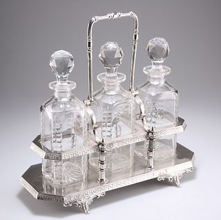 A LATE VICTORIAN SILVER-PLATED THREE-BOTTLE TANTALUS, with scroll feet and