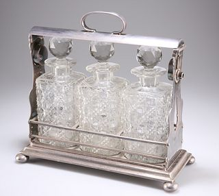 A LATE VICTORIAN SILVER-PLATED THREE-BOTTLE TANTALUS, with bun feet, the cu