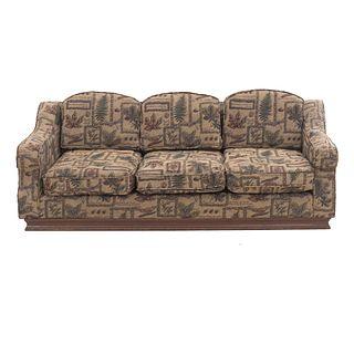 Sofá de 3 plazas. SXX. Estructura de madera con tapicería de tela en tono café con acojinados y soporte tipo zócalo.