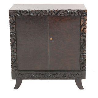 Gabinete. SXX. Estilo Barroco español. Talla en madera. Puertas abatibles y 2 entrepaños al interior. Decorado con motivos orgánicos.