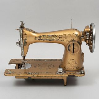Máquina de coser. SXX. De la marca Singer. Elaborada en metal dorado. Decorada con motivos florales. 28 x 40 x 18 cm.