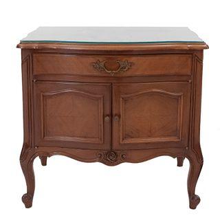 Mesa de noche. SXX. Estilo Luis XV. Elaborada en madera, con cubierta de vidrio. 2 Puertas abatibles, un cajón. 60 x 62 x 45 cm.
