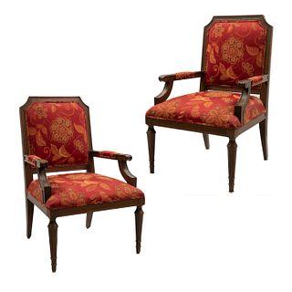 Par de sillones. Siglo XX. Estructura de madera. Con asientos y respaldo en tapicería de tela roja con motivos florales.