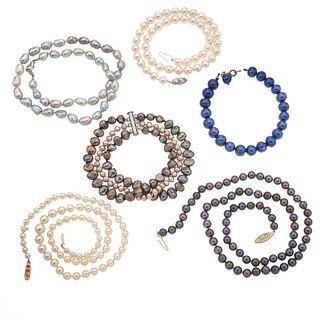 Cuatro collares y 2 pulseras con perlas cultivadas en color crema, gris, azul, café.
