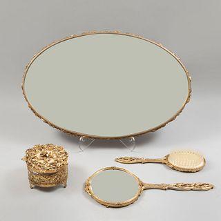 Juego de tocador. SXX. Elaborado en metal dorado y vidrio. Decorados con motivos florales, vegetales y orgánicos. Piezas. 4