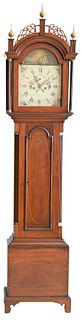 Peregrine White Cherry Tall Case Clock having fretwork top with three finials over tombstone door, flanked by fluted columns, over arched molded door
