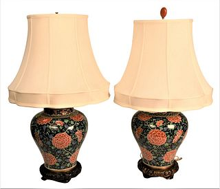 Pair of Chinese Famille Rose Porcelain Covered Urns having black ground with scrolling green and blue vines and leaves, large red flowers on metal bas