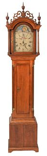 Timothy Barnes Cherry Tall Clock having fret work top with three wood finials supported by fluted columns over long door flanked by fluted columns, al