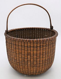 Nantucket Swing Handle Basket  having minute damage near bottom height 8 inches plus handle, diameter 11 1/4 inches Provenance: Fifty Year Personal Co