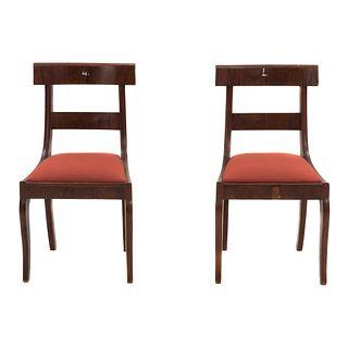 Par de sillas. México, SXX. Elaboradas en madera. Con respaldos escalonados y asientos en tapicería textil. De la firma López Morton.