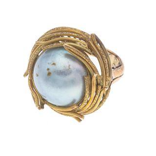 Anillo con media perla en oro amarillo de 14k. 1 media perla color gris de 18 mm. Talla: 5. Peso: 14.1 g.