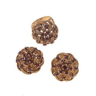 Anillo y par de aretes con granates en oro amarillo de 14k. 44 granates corte redondo. Talla: 5. Peso: 33.9 g.