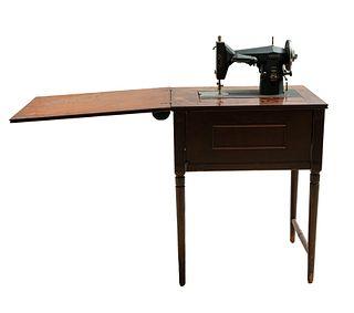 Máquina de coser eléctrica. Estados Unidos, SXX. Marca Kenmore. Mueble elaborado en madera y máquina de metal.