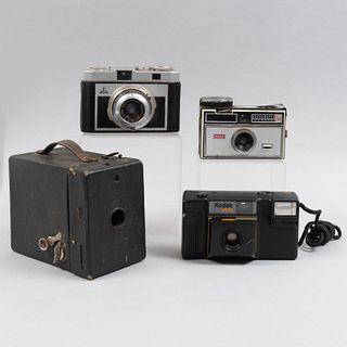 Lote de 4 cámaras fotográficas una Eastman Kodak de caja. SXX. Elaboradas en cartón, resina, cristal y metal.