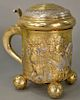 Austrian silver and gilt tankard with stepped top over gilt embossed body with king and knights at castle, all set on four embossed ...