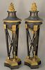 Pair of gilt and bronze torcheres having flame tops on supported stands with paw feet on gilt bronze base on bronze (in three parts)...