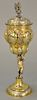Russian silver gilt chalice having cover with finial, lobbed body held by putti on round base with overall gilt decoration, marked:...