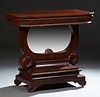 American Classical Carved Mahogany Petticoat Table, 19th c., the canted corner top over a wide skirt on a U-shaped support with a ce...