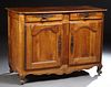 French Provincial Louis XV Style Carved Walnut Sideboard, 19th c., the rounded corner top over two frieze drawers, above double cupboar