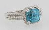 Lady's 14K White Gold Dinner Ring, with a cushion cut 4.8 carat blue zircon, atop a border of tiny round diamonds, the triple split...