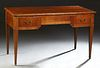 French Louis XVI Style Inlaid Cherry Desk, early 20th c., the stepped ogee edge top over a center frieze drawer flanked by two drawe...