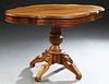 French Carved Walnut Center Table, c. 1870, the stepped tortoise top over a wide skirt with two side drawers, on a turned and reeded...