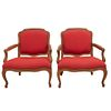Pair of armchairs. 20th century. Carved in wood. With closed backrests and seats in red upholstery, semi-curved shafts.