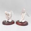 Pareja de ángeles. España. Años 90.  En porcelana Lladró. Acabado gress. Con certificados y bases de madera. 20 x 15 x 18 cm.