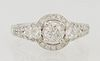 Lady's 14K White Gold Dinner Ring, with a central .53 carat round diamond atop a border of small round diamonds, flanked by diamond...