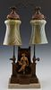 German Art Nouveau Patinated Spelter Table Lamp, c. 1910, with a seated female figure on a chair flanked by two columns, rising and bending over to tw