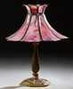 American Gilt Spelter Table Lamp, c. 1920, on a tapered baluster support to a relief decorated circular base, with a later pink floriform slag glass s