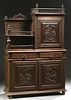 French Provincial Henri II Style Carved Oak Buffet a Deux Corps, c. 1880, Brittany, the spindled crown over a figural carved cupboard door right with