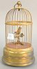 "Singing bird in brass cage, in working condition, ht. 11""."