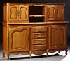 French Carved Cherry Buffet a Deux Corps, 20th c., the rounded edge serpentine top with central open storage flanked by double cupbo...