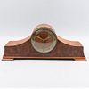 Reloj de mesa. Siglo XX. Elaborado en madera con aplicaciones de metal. Mecanismo de cuerda. Carátula circular e índices arábigos.