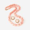 A coral and fourteen karat gold necklace with matching ear clips,