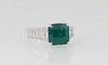 Lady's 18K White Gold Dinner Ring, with a 3.35 ct. square emerald atop graduated shoulders with a central row of baguette diamonds, flanked by edge r