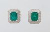 Pair of Platinum Earrings, with a central 1.98 ct. emerald atop a double concentric graduated border of round diamonds, with a screw post, total emera