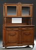 French Louis XVI Style Carved Oak Buffet a Deux Corps, early 20th c., the ribbon carved crest over a stepped crown above double wide beveled glass cup