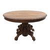 Mesa pedestal.  Francia.  Siglo XX.  En talla de madera de nogal.  Con cubierta circular, fuste compuesto y soportes tipo garra.