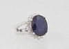 """Lady's 14K White Gold Dinner Ring, with an oval 8.97 ct. blue sapphire atop a border of round diamond """"points,"""" on a split shoulder band mounted with"""