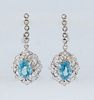 Pair of 14K White Gold Hoop Earrings, the diamond mounted half-hoops with a pendant oval blue zircon atop a pierced diamond mounted border, total zirc